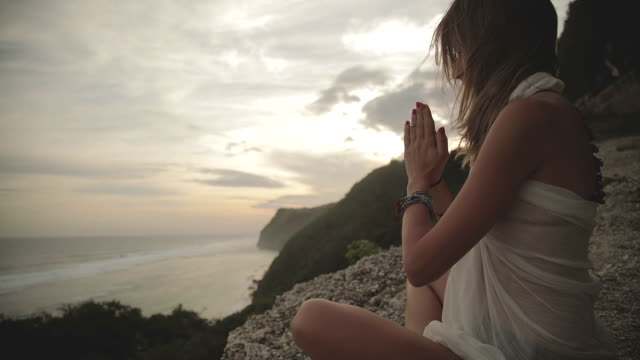 young woman practicing yoga on the beach. - mindfulness stock videos & royalty-free footage