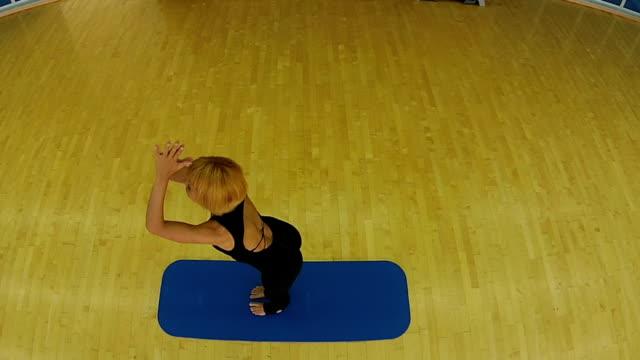 junge frau übt yoga auf der matte im fitnessstudio - haarfarbe stock-videos und b-roll-filmmaterial