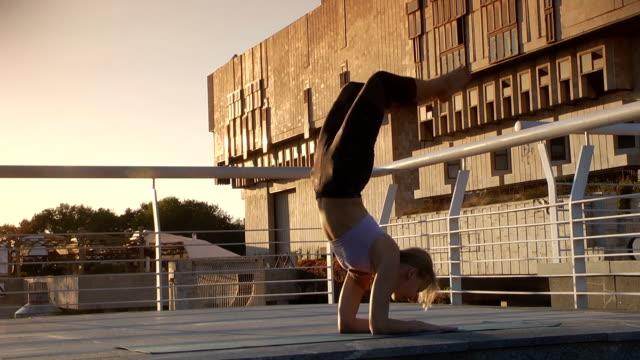 若い女性ヨガを練習。サソリのポーズ。 ビデオ