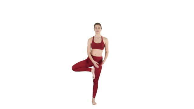 Young woman practicing yoga, standing in Utthita Hasta Padangustasana exercise, Extended Hand to Big Toe pose on white background