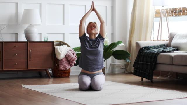 giovane donna che pratica yoga in soggiorno a casa - yoga video stock e b–roll