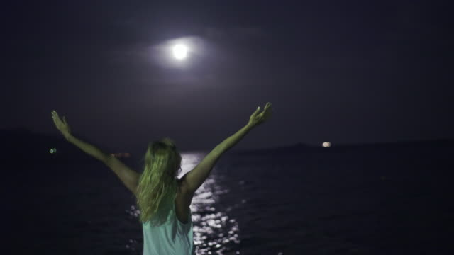 Young woman pray on the shore. Full moon. video