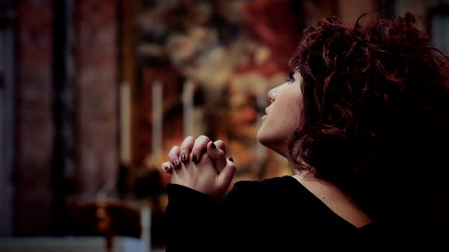 young woman praying and whispers something to God video