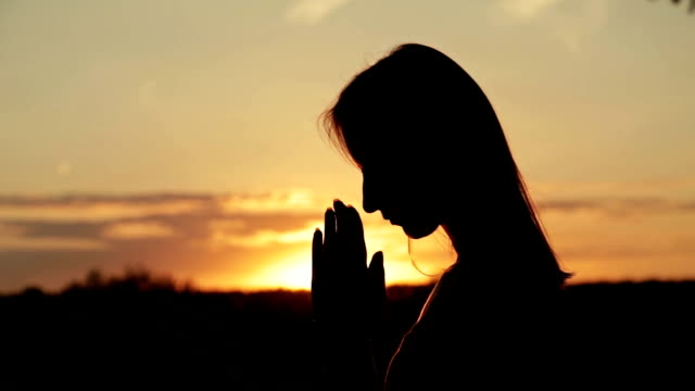 Young woman praying in the forest at sunset video