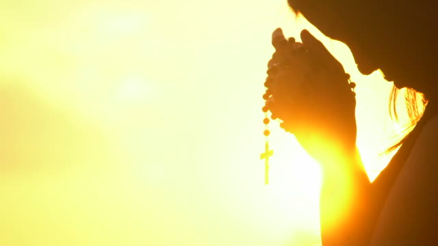 young woman praying with cross on beautiful sunset - религиозные тексты стоковые видео и кадры b-roll