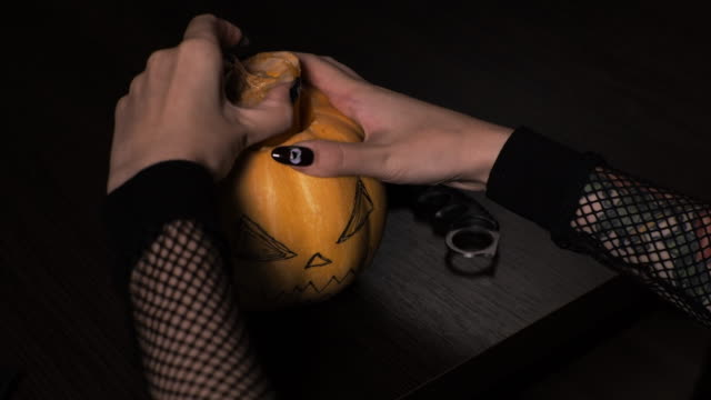young woman prepares a pumpkin for halloween. cuts out the inside. holiday. - zucca legenaria video stock e b–roll