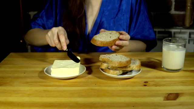 Young woman preparing a sandwich, spreads butter on bread. video