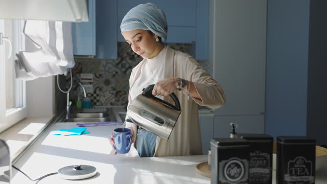 Young woman preparing hot tea cup for breakfast video