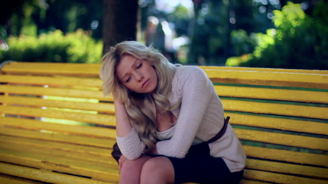 Young woman problems, depression, headache sad sits in park video
