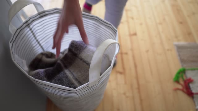 vídeos de stock e filmes b-roll de a young woman pulls a woolen knitted blanket from a laundry basket, on a wooden floor background - hygge