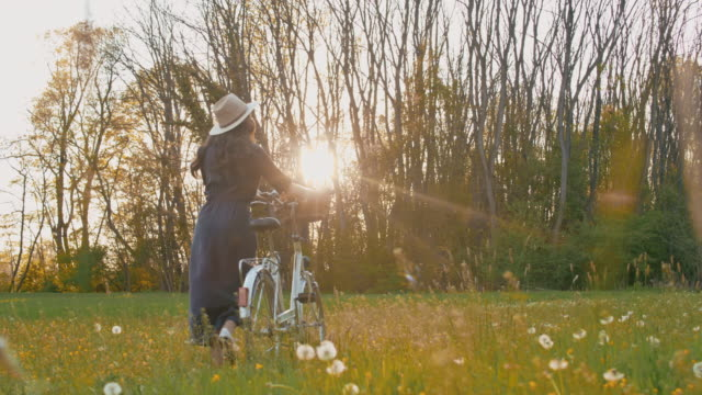 SLO MO WS Young woman pushing her bicycle through meadow