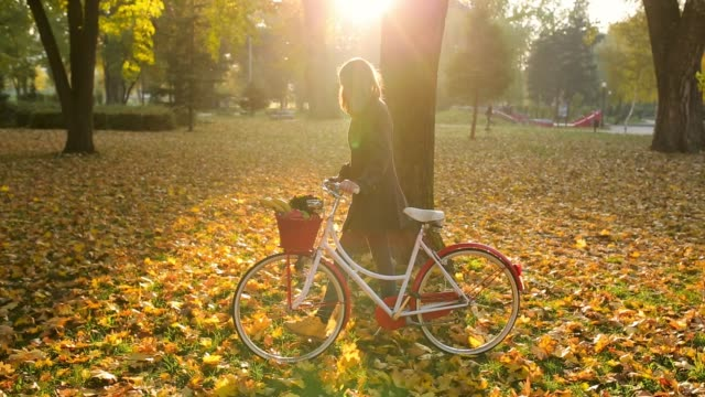Young woman pushing retro bike with basket on front in public park. Idyllic autumn day