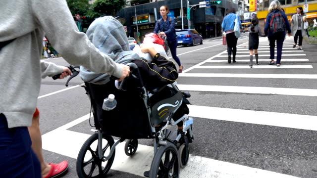 若い女性が通りを横断する車椅子の年配の女性を押す - 介護点の映像素材/bロール