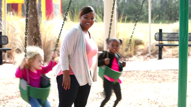 Young woman pushing two little girls on swings video