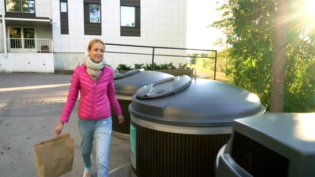 vídeos y material grabado en eventos de stock de una joven que pone diferentes tipos de basura en diferentes contenedores de reciclaje - suministros escolares