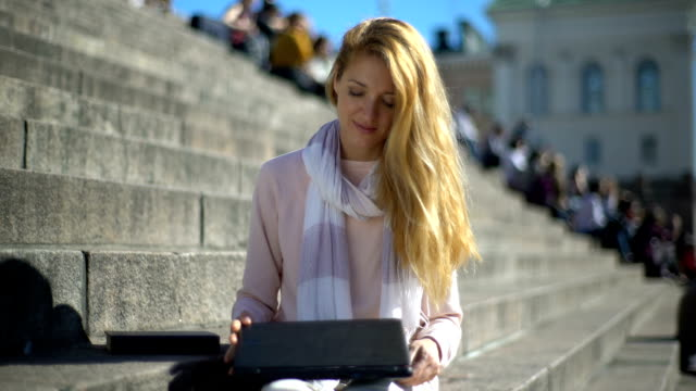 Young woman puts aside the laptop and picks up a book on the stairs in the center of the city. video