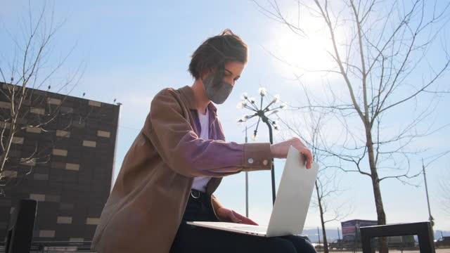 молодая женщина надевает на лицо медицинскую маску в городском парке - covid testing стоковые видео и кадры b-roll