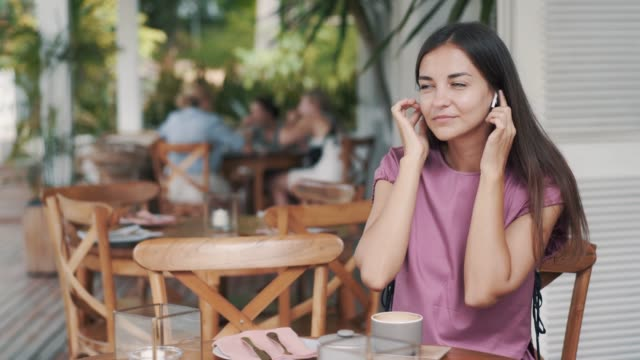 young woman puts on wireless earphones, listens to music and dances in cafe - cuffie wireless video stock e b–roll
