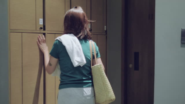 Young woman puts the bag in a locker storage in Gym Young asian woman walking to her locker and opening her bag at the locker gym. Thailand. locker stock videos & royalty-free footage