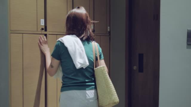 vídeos de stock, filmes e b-roll de mulher jovem coloca o saco em um armazenamento de cacifo no ginásio - armário com fechadura