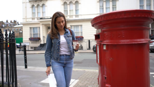 Young woman putting a letter in the mail while enjoying a take out coffee Young woman putting a letter in the mail while enjoying a take out coffee - City lifestyles post office stock videos & royalty-free footage