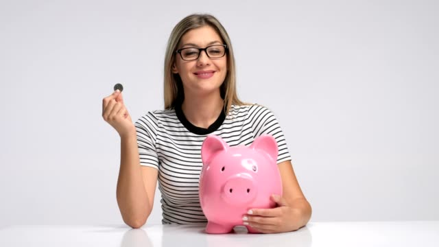 Young woman putting coin inside piggybank and pointing up video