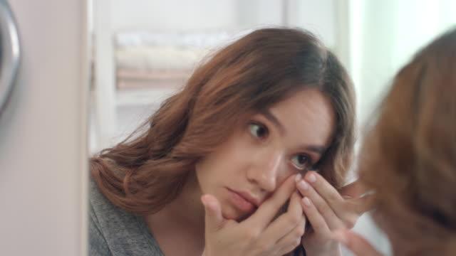 vídeos de stock e filmes b-roll de young woman putting contact lens for eye front bathroom mirror in home - contacts