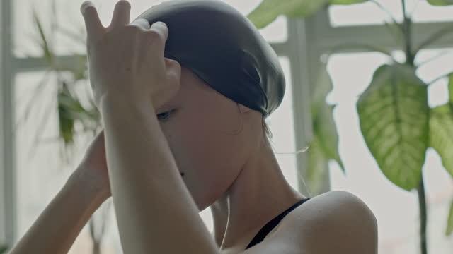 vídeos de stock, filmes e b-roll de jovem mulher colocando uma touca de natação - câmera lenta, close-up - boné