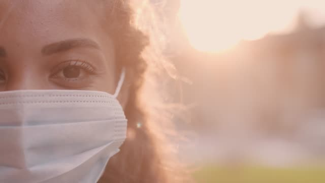 young woman putting on and adjusting her protective face mask - vestirsi video stock e b–roll