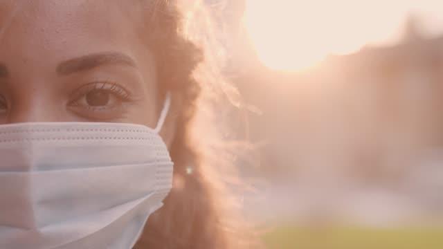 vídeos y material grabado en eventos de stock de mujer joven poniéndose y ajustando su máscara protectora de la cara - face mask