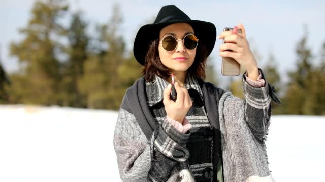stockvideo's en b-roll-footage met jonge vrouw make-up op te zetten in de winter - lipbalsem