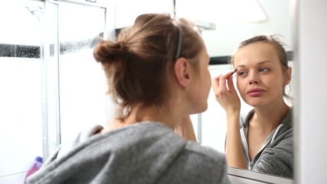 vidéos et rushes de jeune femme faisant de maquillage - fard à paupières