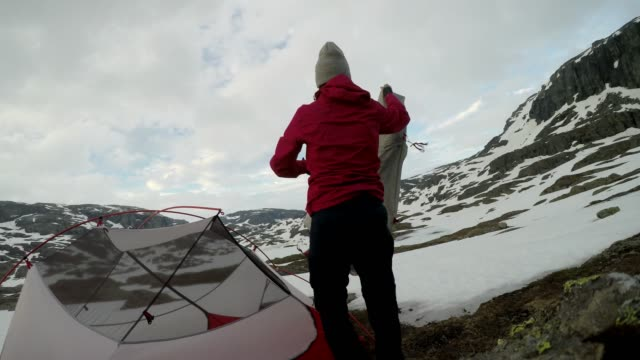 A young woman putting up the tent in the nearby of Trolltunga, Norway. Wild camping in the nature. Couple is having fun. They are surrounded by snow. Winter mountain climbing. Freedom and adventure.