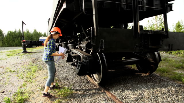 A young woman railroader checks of the axle-box of the freight wagon. video
