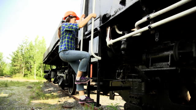 A young woman railroader get down the stairs and walking next to train. video