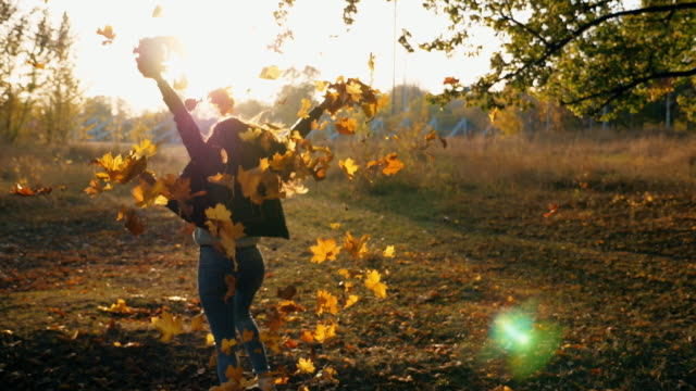 vídeos de stock e filmes b-roll de young woman raising her hands and spinning around scattering autumn leaves. happy girl showing joyful emotions with sunset at background. lady enjoying beautiful autumn environment. slow motion close up - folha vermelha