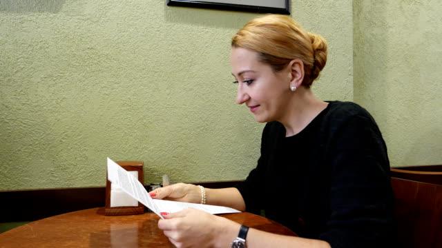 ung kvinna läsa tryckta brev med liten leende, sedan bli allvarliga - e post bildbanksvideor och videomaterial från bakom kulisserna