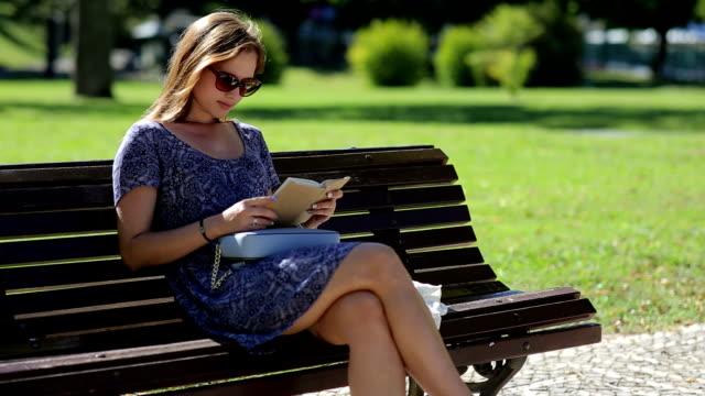 Jonge vrouw het lezen van een boek en zittend op een bankje buiten in een park in de zomer, in zonnebrillen video