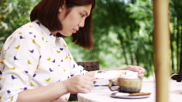 Young woman reading a book at outdoor zone coffee cafe video