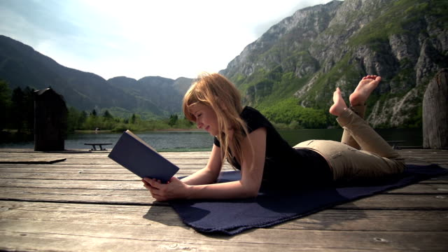 Young woman reading a book by a lake in mountains video