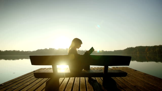 Young woman reading a book by the lake video