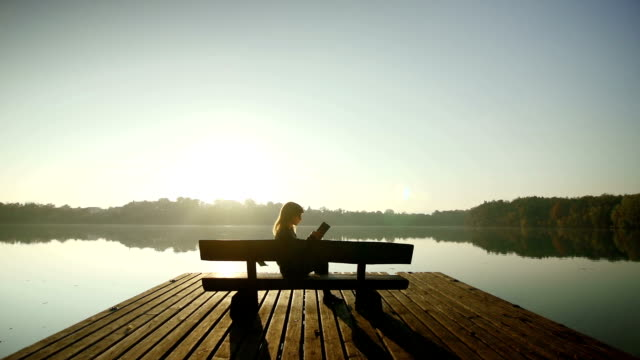 Young woman reading a book on a bench by lake video