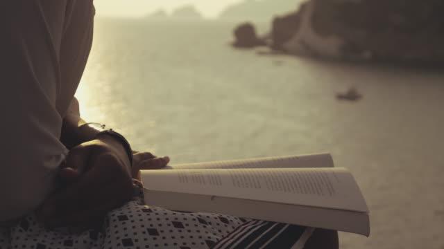 stockvideo's en b-roll-footage met jonge vrouw het lezen van een boek zittend op een muur op het strand bij zonsondergang op het eiland ponza, italië. mode wit overhemd en rok. - literatuur