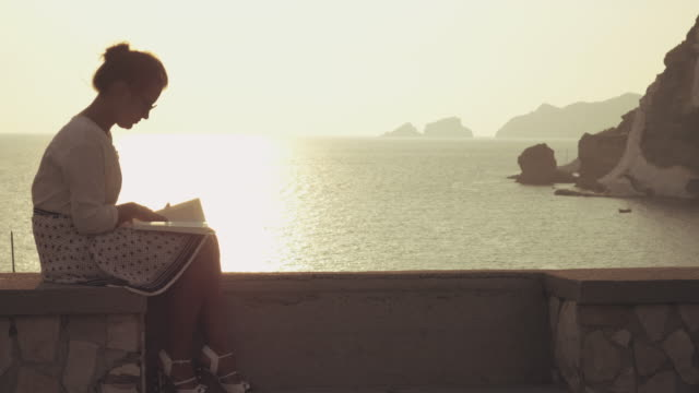 Young woman reading a book sitting on a wall at the beach at sunset on Ponza Island, Italy. Fashion white shirt and skirt.