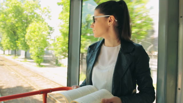 Young woman reading a book while traveling with the tram. video
