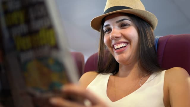 Young woman reading a newspaper in a ferry