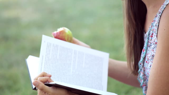 Young woman reading book and eating apple in park. video