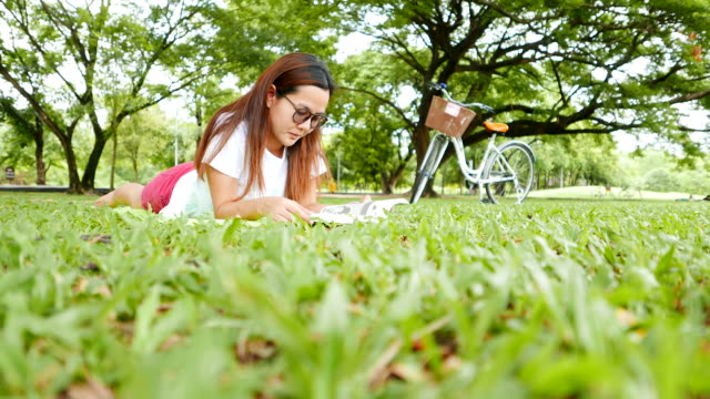 Young Woman Reading Book and Using Smartphone in Park video