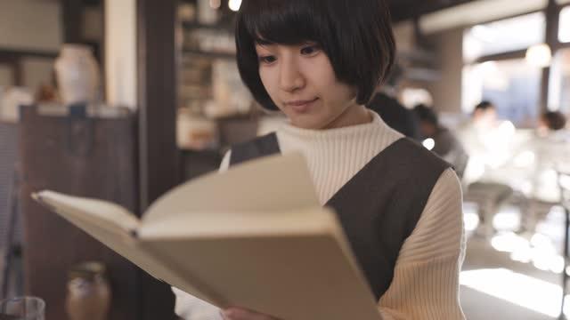 古い和食レストランで読書をする若い女性 - 本点の映像素材/bロール