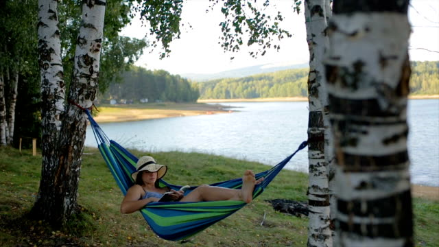 young woman reading book in the nature - amaca video stock e b–roll